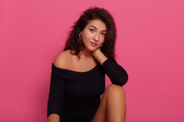 ピンクの壁に対して自信を持ってポーズをとって穏やかなロマンチックな女性