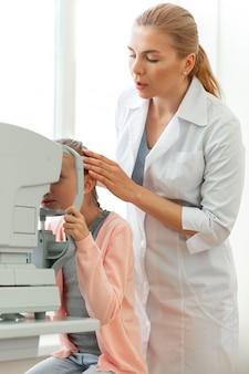 Нежный серьезный офтальмолог исправляет положение молодой пациентки. Premium Фотографии