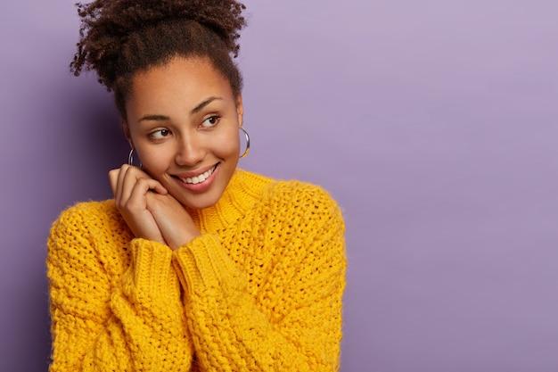 優しい笑顔の暗い肌の女性モデルは、喜んで脇に見え、顔の近くで手をつないで、望ましいことに気づき、黄色いニットのセーターを着ています