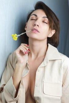 Нежный мягкий домашний портрет женщины в бежевом пиджаке с желтым цветком в оправе