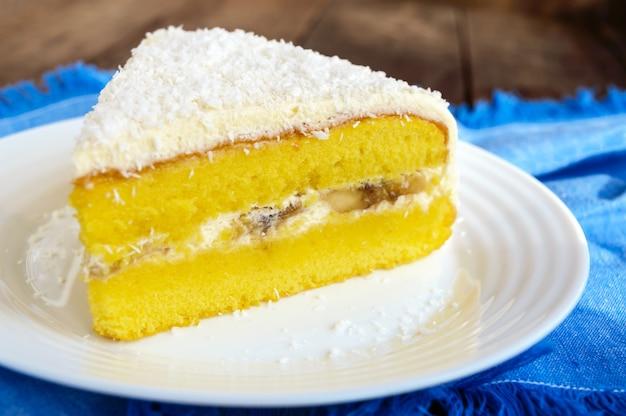 クリーミーなバナナの層が付いた優しいスポンジケーキ、上にココナッツを振りかける