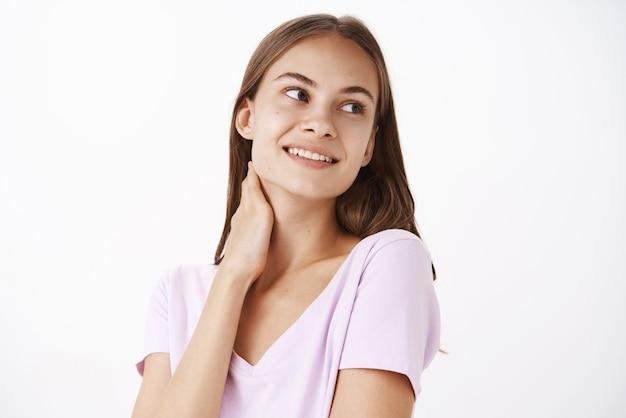 Dolce e tenera giovane femmina bruna femminile in maglietta casual che tocca il collo e guarda a destra con un sorriso sensuale e carino sentirsi carina con la pelle pulita e pura dopo aver applicato la crema quotidiana