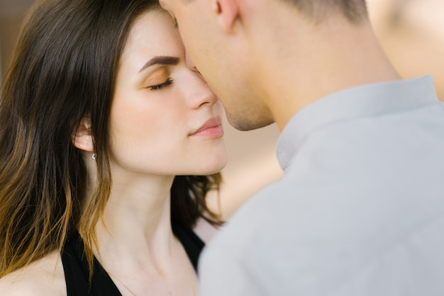 Gentle and tremulous kiss on the nose of a guy and a girl