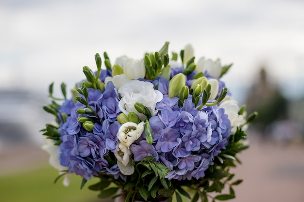 Gentle wedding bouquet of hydrangeas, roses and freesia on blurred wooden background. wedding details in blue and white colors.gorgeous wedding bridal bouquet. flowers at the wedding ceremony.