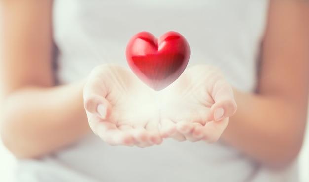 優しい女性の手と彼の手で輝く赤いハート。バレンタインの母の日とチャリティーの概念。