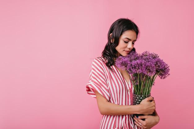 ロマンチックな気分の優しい若い女性は、花の腕一杯を見てかわいいです。スタイリッシュな服装のヨーロッパの女性の肖像画。
