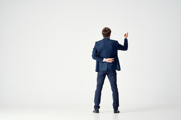 Gentleman in a blue suit gestures with his hands on a light back view business finance