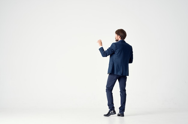 Gentleman in a blue suit gestures with his hands on a light space back view business finance