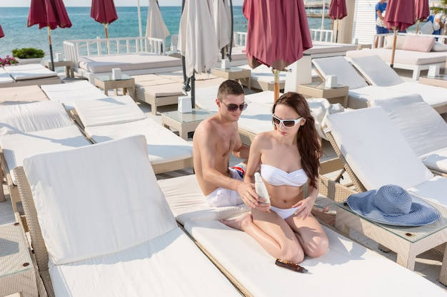 Gentleman helping her girlfriend putting sunscreen lotion while sitting on the loungers in the resort on a tropical climate.