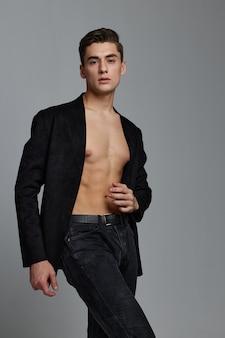 Джентльмен в классическом костюме на голом теле на серой стене.