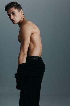灰色の背景、裸の胴体、背面図に暗い服を着た紳士。高品質の写真