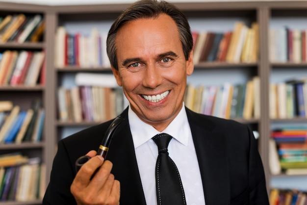 パイプを持つ紳士。パイプを保持し、本棚に立って笑っている正装で自信を持って成熟した男の肖像画