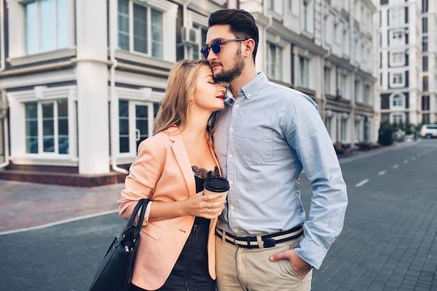 Delicatamente coppia sta abbracciando sulla strada in città. bel ragazzo è camicia blu e occhiali da sole sembra seriamente, bella ragazza bionda in abito nero coccole a lui.
