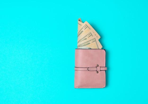 青色の背景にドルで優しくピンクの財布。買い物に行きましょう!