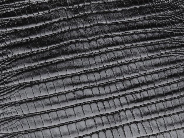 Genuine black reptile skin leather texture background. macro photo