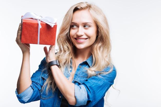 진정한 호기심. 아름 다운 젊은 여자 선물 상자를 들어 올려 회색 배경에 고립 된 서있는 동안 미소와 호기심 표정으로 그것을보고