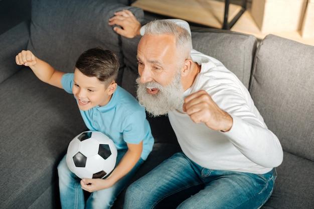 Настоящие эмоции. счастливый мальчик предподросткового возраста и его дедушка сидят на диване и эмоционально празднуют гол, забитый их любимой футбольной командой