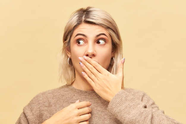 Genuine human emotions, feelings and reaction. attractive blonde young woman having surprised look, trying to keep secret or confidential information, covering mouth with hand and looking away