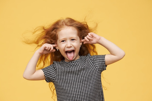 Genuine human emotions, reaction and body language. angry spoiled little girl with red hair sticking out tongue, pretending not to hear you, plugging ears, screaming, being mad and naughty