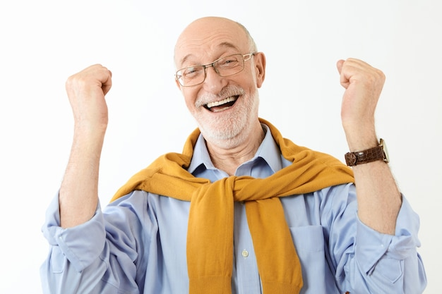 Подлинные человеческие выражения лица, чувства и реакция. симпатичный стильный пенсионер в очках и рубашке, восторженный, восторженный вид, сжимающий кулаки, взволнованный успехом или хорошими новостями