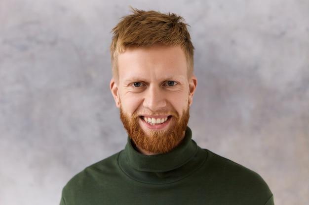 진정한 인간의 반응, 감정, 삶의 지각 및 태도. 이빨 미소로 좋은 소식에 기뻐하는 롤 넥 스웨터를 입고 카리스마 긍정적 인 생각 젊은 수염 난 남자