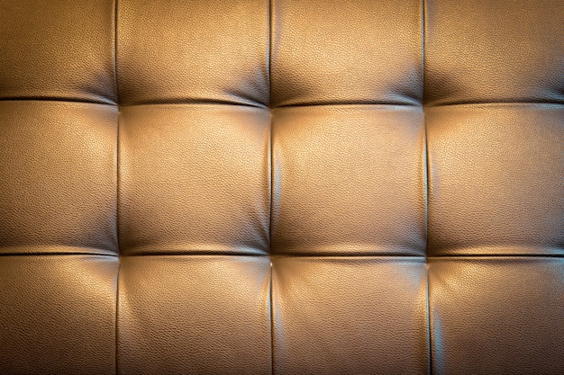 Genuine leather upholstery background for a luxury decoration in golden tone