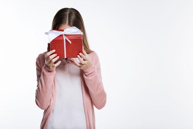 정말 부끄러워. 회색 배경에 고립 포즈를 취하는 동안 선물 상자 뒤에 그녀의 얼굴을 숨기는 귀여운 십 대 소녀