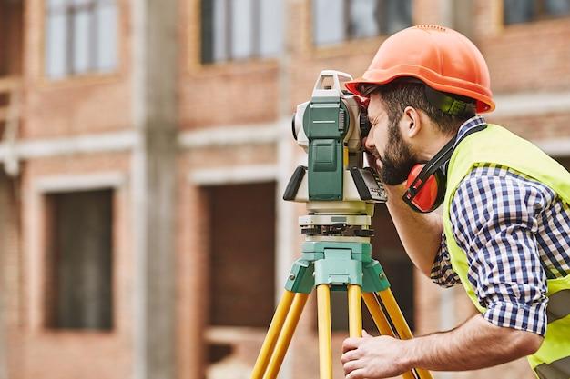 Инженер-геодезист геодезических работ в защитной одежде и красной каске с использованием геодезического оборудования на