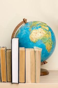 地理的な地球儀とテーブルの上の本