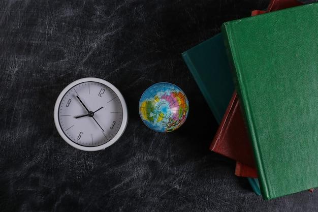 Урок географии. стопка книг, часов и земного шара на доске мелом. обратно в школу. вид сверху