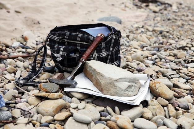 돌과 메모 용지가 있는 지질학자 가방 지질학 지질학자 망치와 자갈에 광물