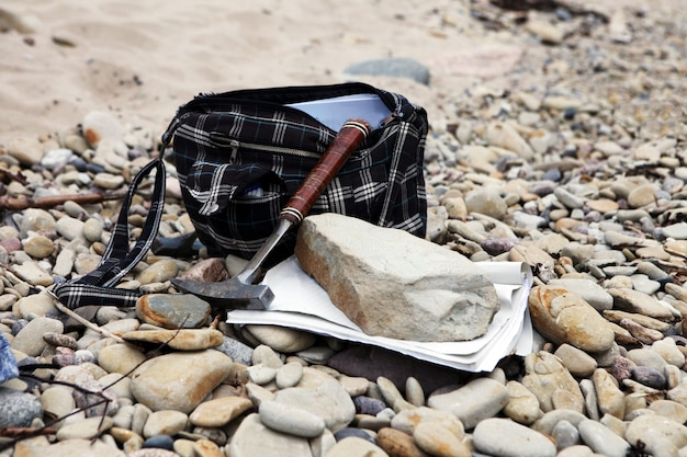 Geologist bag with stones and notes papers geology science geologist hammer and mineral on pebbles