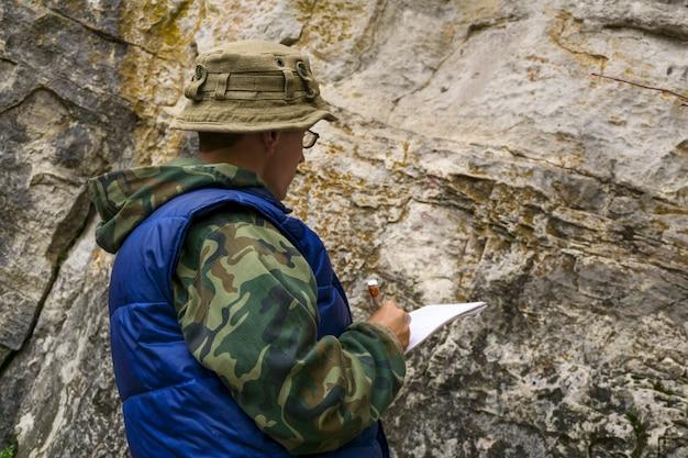 지질학자는 표면 지질 조사 작업 중 암석 노두에 대한 설명을 수행합니다.
