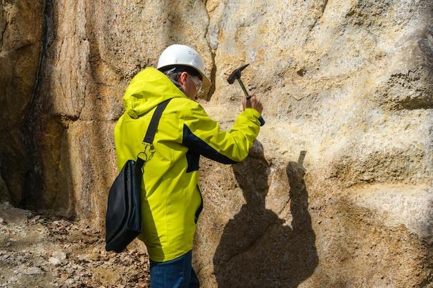 헬멧을 쓴 지질학자는 망치로 바위를 두드려 광물 표본을 채취한다