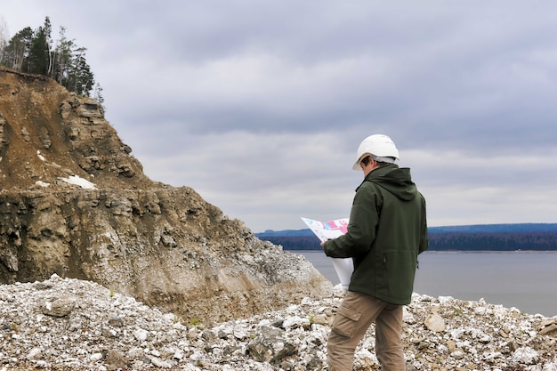 Геолог с картой у скалистого берега реки