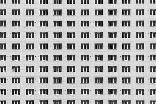 Geometric background with lots of window rows. modern building texture. office construction. apartment building close-up. many windows on huge wall. european classic high-rise building with copy space