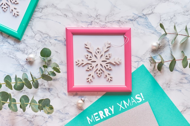 기하학적 크리스마스 평면 분홍색과 녹색 프레임 평면도. 신선한 유칼립투스 나뭇 가지와 핑크 프레임에 장식 흰색 반짝이 눈송이.