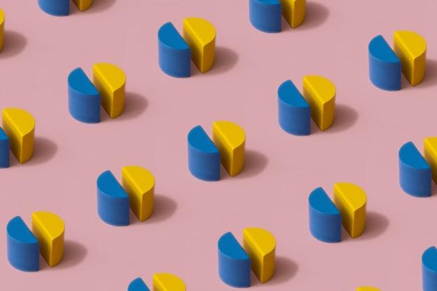 パステルピンクの背景に青と黄色の木の形で作られた幾何学的な構成