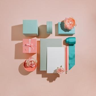 꽃, 카드 모형, 파스텔 음소거 색상의 초대장이있는 선물 상자의 기하학적 구성. 청첩장에 대 한 낭만적 인 개념 레이아웃