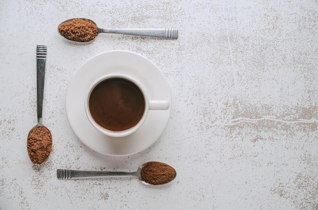 재료가 포함된 3개의 숟가락과 갓 준비한 초콜릿 한 컵의 기하학적 구성