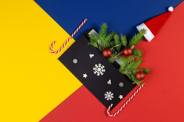 Geometric creative christmas flat lay with black envelope. above view of multicolored geometric layered paper background in yellow, blue, red. christmas new year minimal concept with copy space.