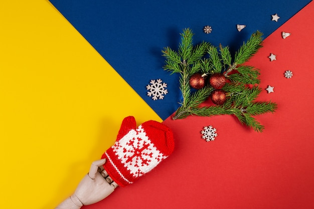 Geometric creative christmas flat lay with christmas tree branch. above view of multicolored geometric layered paper background in yellow, blue, red. christmas new year minimal concept