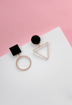 Серьги с геометрическим дизайном на белой и розовой поверхности с копией пространства