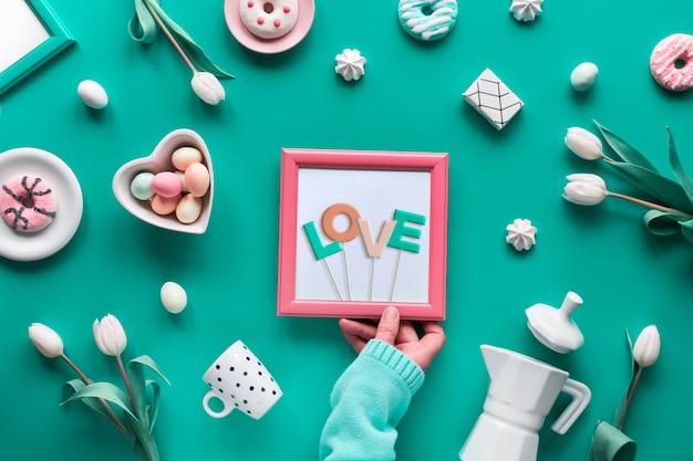 幾何学的なイースターまたは母の日の配置。テキスト「愛」、手にフレーム。緑のミントの壁に白、ピンクの装飾が施されたフラット甘い卵、コーヒーメーカー、カップ、花、お菓子。