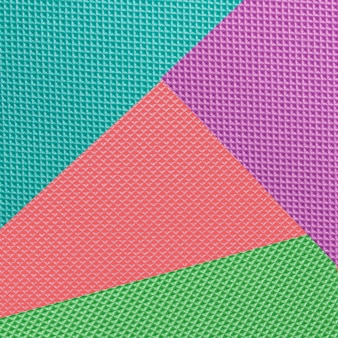 Geometric flat lay blue, green, coral and violet texture background
