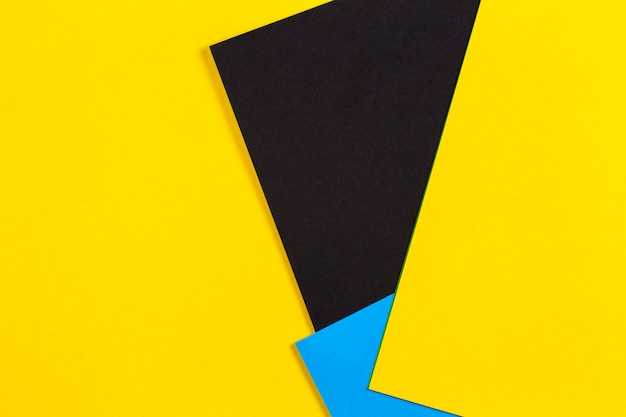 Geometric flat lay yellow blue and black color paper wall