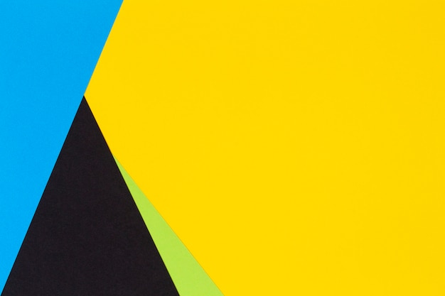 Geometric flat lay yellow green blue and black color paper wall