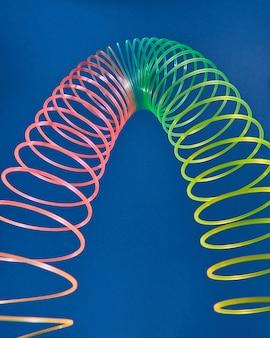 복사 공간 파란색 배경에 유연한 무지개 봄 장난감에서 만든 기하학적 형태 곡선 포물선.