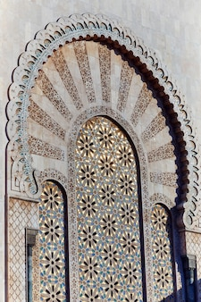イスラム教のモスクの幾何学的なイスラム教徒のモザイク、美しいアラビアのタイルパターンとモロッコのカサブランカ市のモスクの壁とドアのモザイク