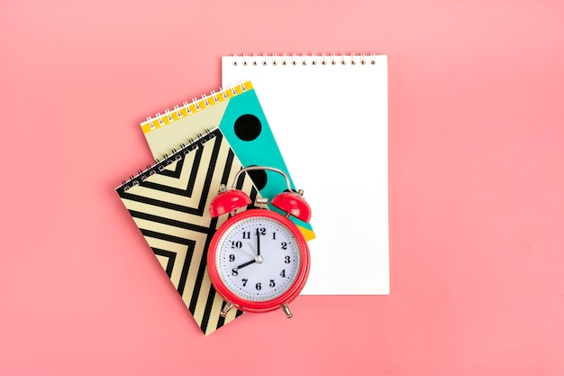 Geometric notebooks and alarm clock on pink stationary, back to school concept  flat lay
